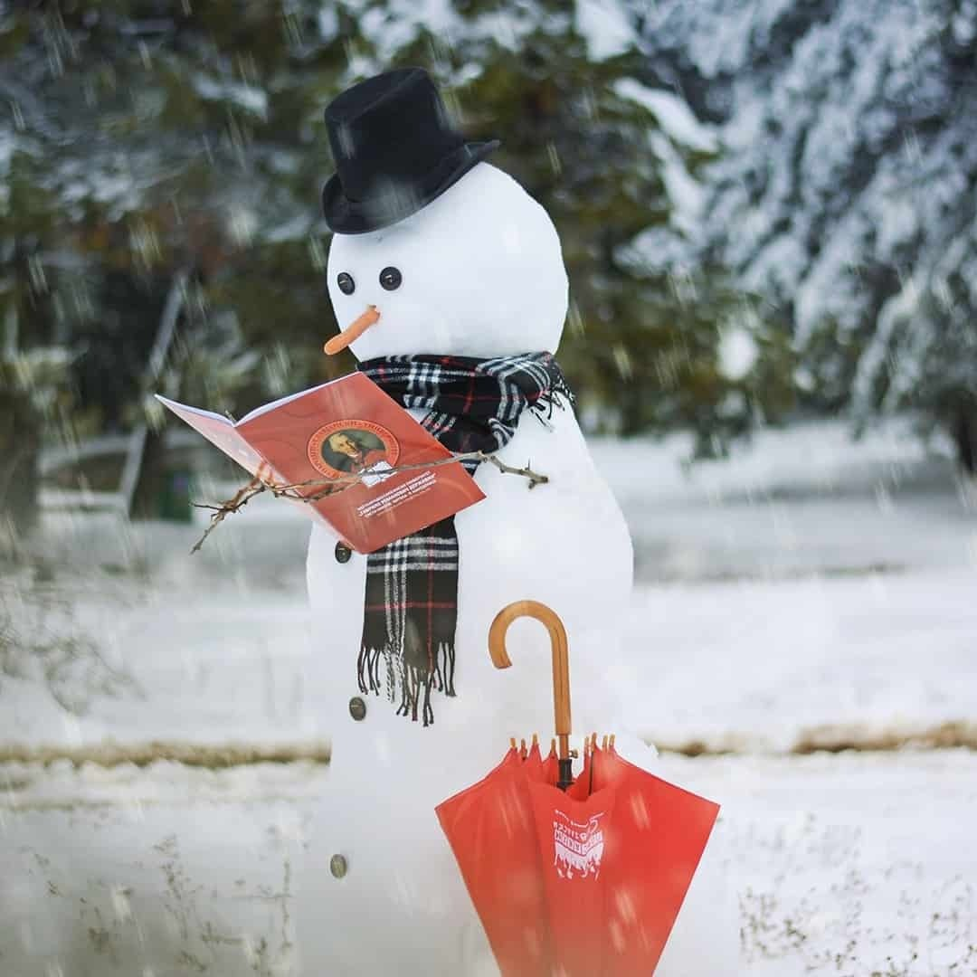 An image of a snowman reading about International Slavic University G. R. Derzhavin, with red umbrella next to it, while the snow is falling down.