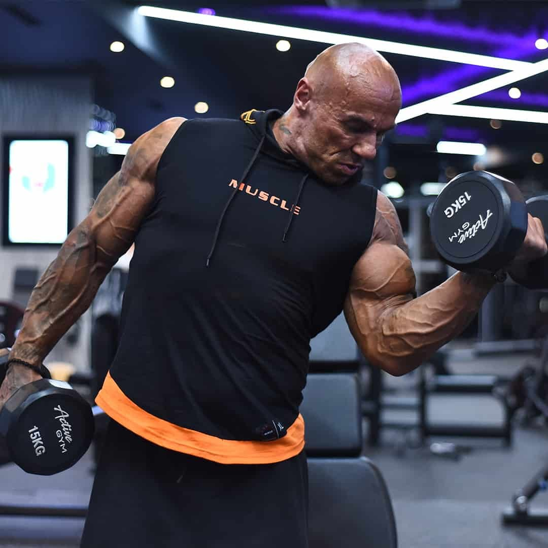 Tose Zafirov training his biceps with weights at the gym, while wearing black t-shirt with orange details and black shorts.