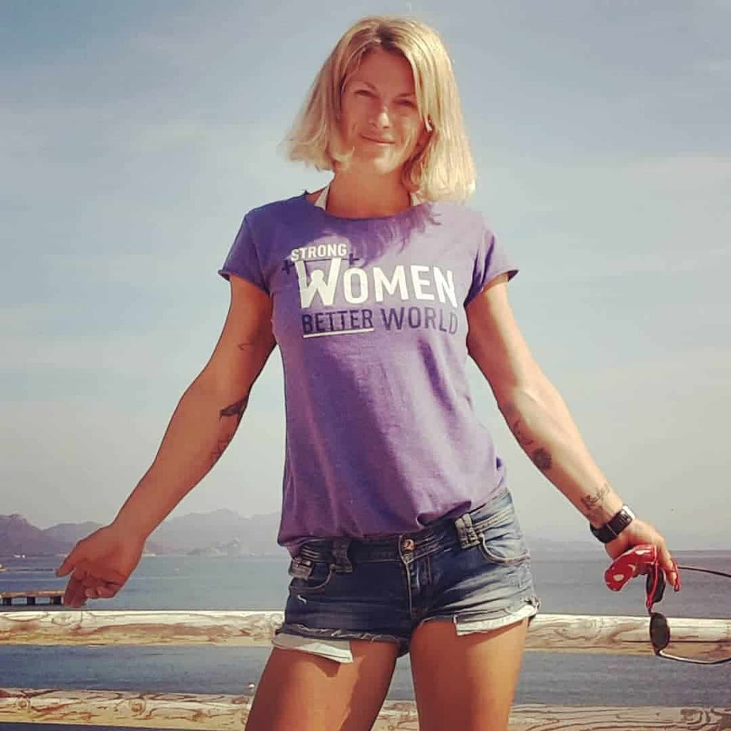 Ilinsa Arsova standing in front of a like and posing in a purple t-shirt with a quote on it ''strong women better world''. She is also wearing shorts.