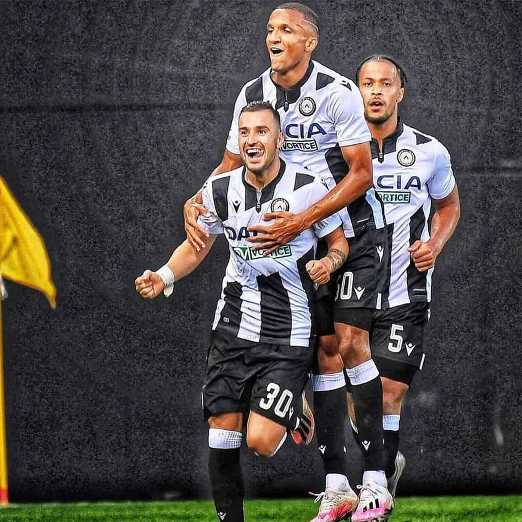 Ilija Nestorovski celebrating after a goal, on the football playground with this teammates. He is smiling and he is wearing white jersey with black details and black shorts.