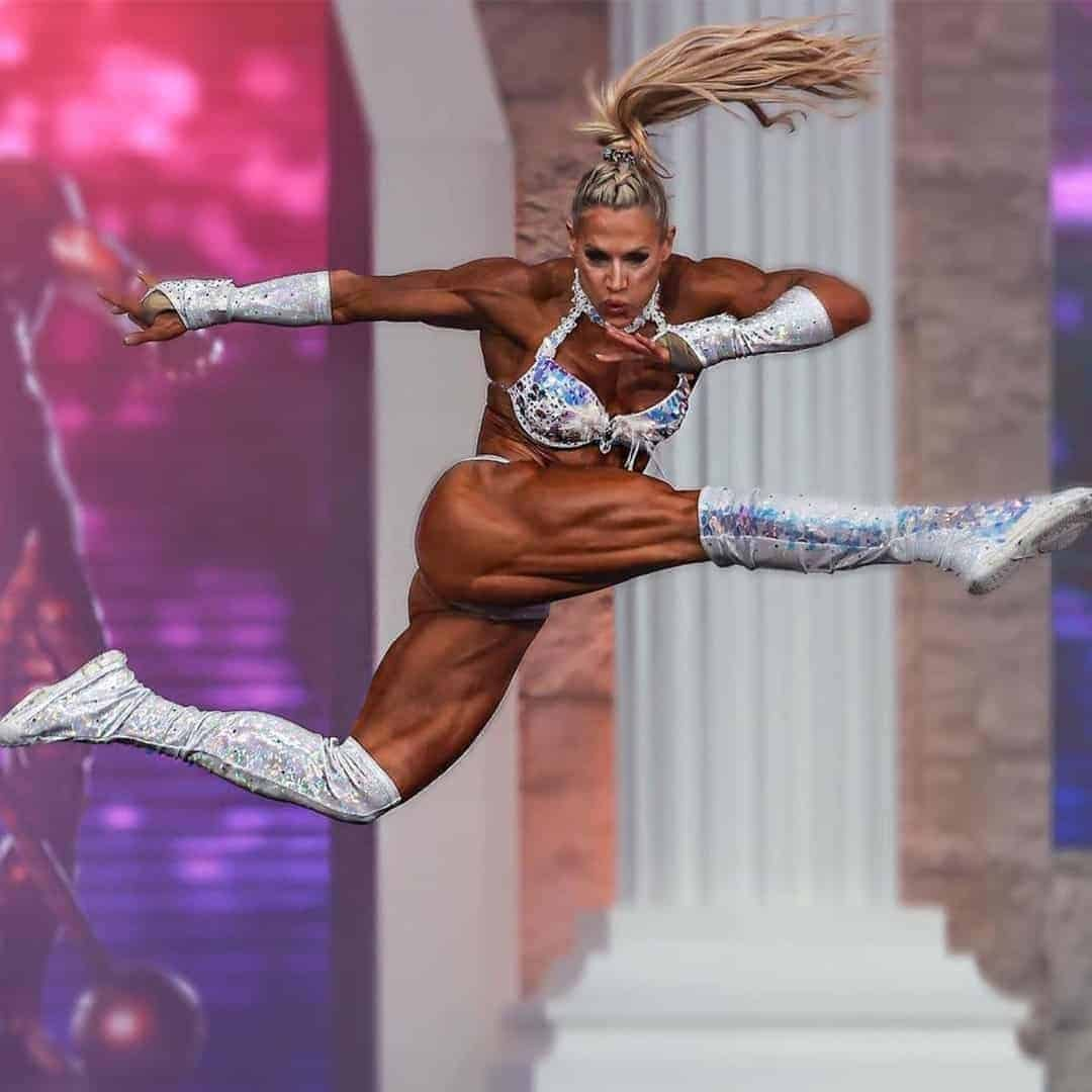 An image of Whitney Jones on stage on Mr. Olympia while doing her performance. She is jumping while wearing silver set.