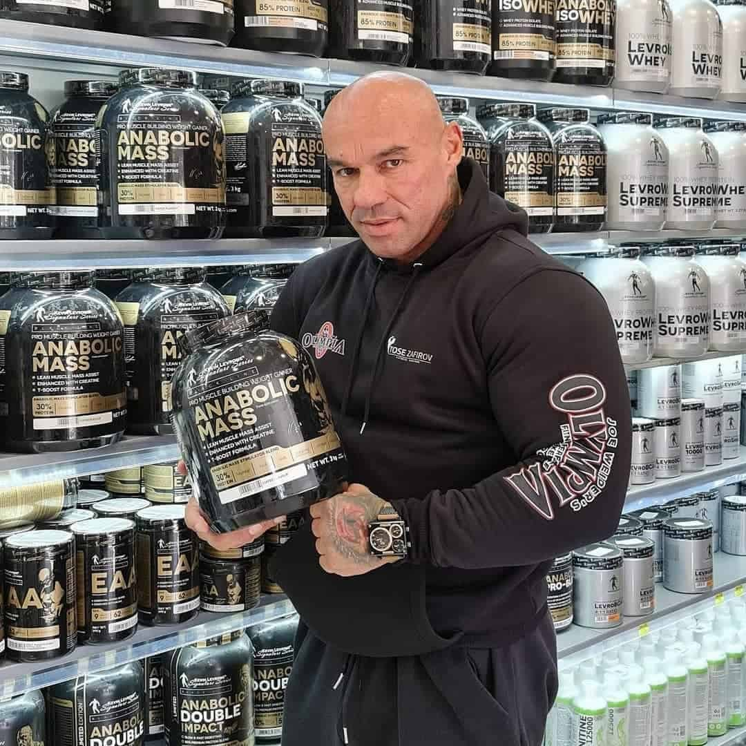 Tose Zafriov in a black Mr. Olympia hoodie, standing in front of a shelf with supplements from the Levrone Black and Signature Line. He is holding anabolic mass from the black line in his hands.