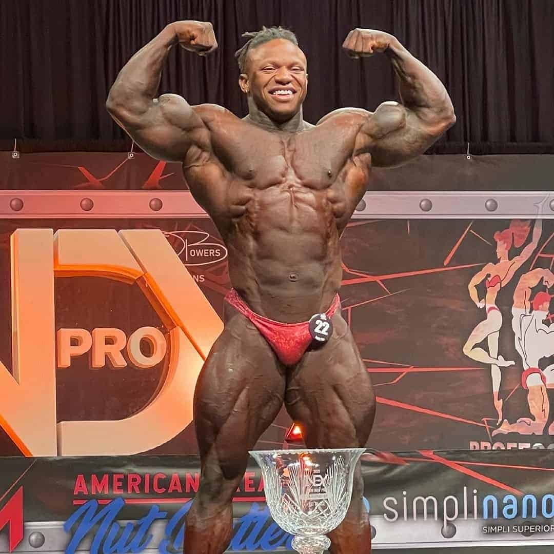 Tonio Burton on the Mr. Olympia stage, with his medal in front of him, he is flexing his muscles and he is wearing red trunks with the number 22 on it.