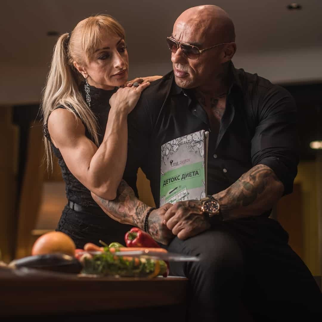 Gabriela Zafirova, in a black, elegant dress staring at Tose Zafirov while he is holding the Detox Diet. Tose is in a black shirt and he is wearing sunglasses on his eyes. There are also some fruits and vegetables in front of them.