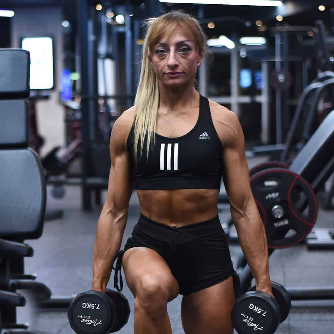 Gabriela Zafirova training at the gym while holding two weights in her hands training her legs. She is wearing black, adidas sports bra, and black shorts.
