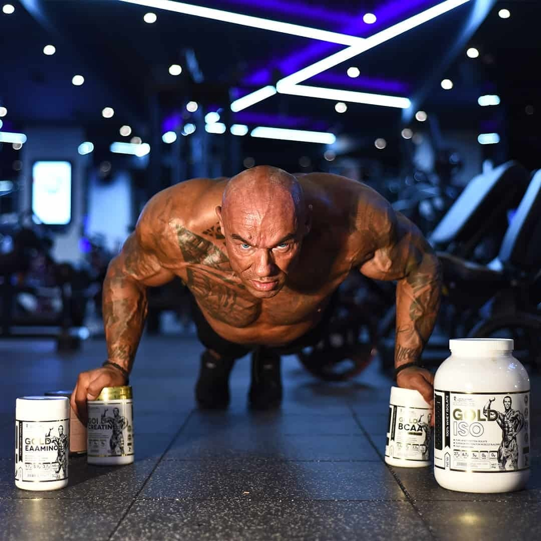 Tose Zafirov in a gym. He is without t-shirt and he is doing push-ups with some products from the Kevin Levrone Signature series in front of him.