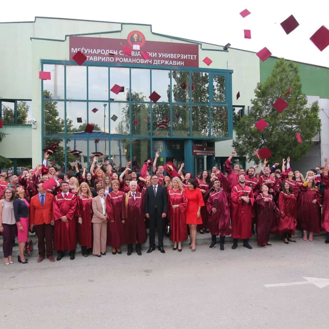 Students graduating at the International Slavic University G. R. Derzhavin. They ae all in front of the university wearing burgundy, elegant clothes and throwing their graduation caps.