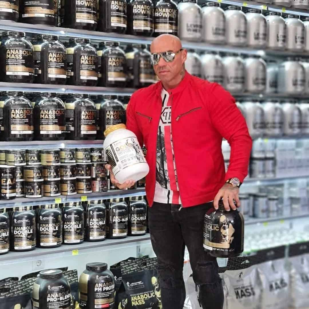 Tose Zafriov in a red jacket, dark grey jeans, and sunglasses on his eyes, standing in front of a shelf with producst from the Levrone signature series and Levrone black line. He is holding they protein from the gold line, and anabolic mass from the black line in his hands.