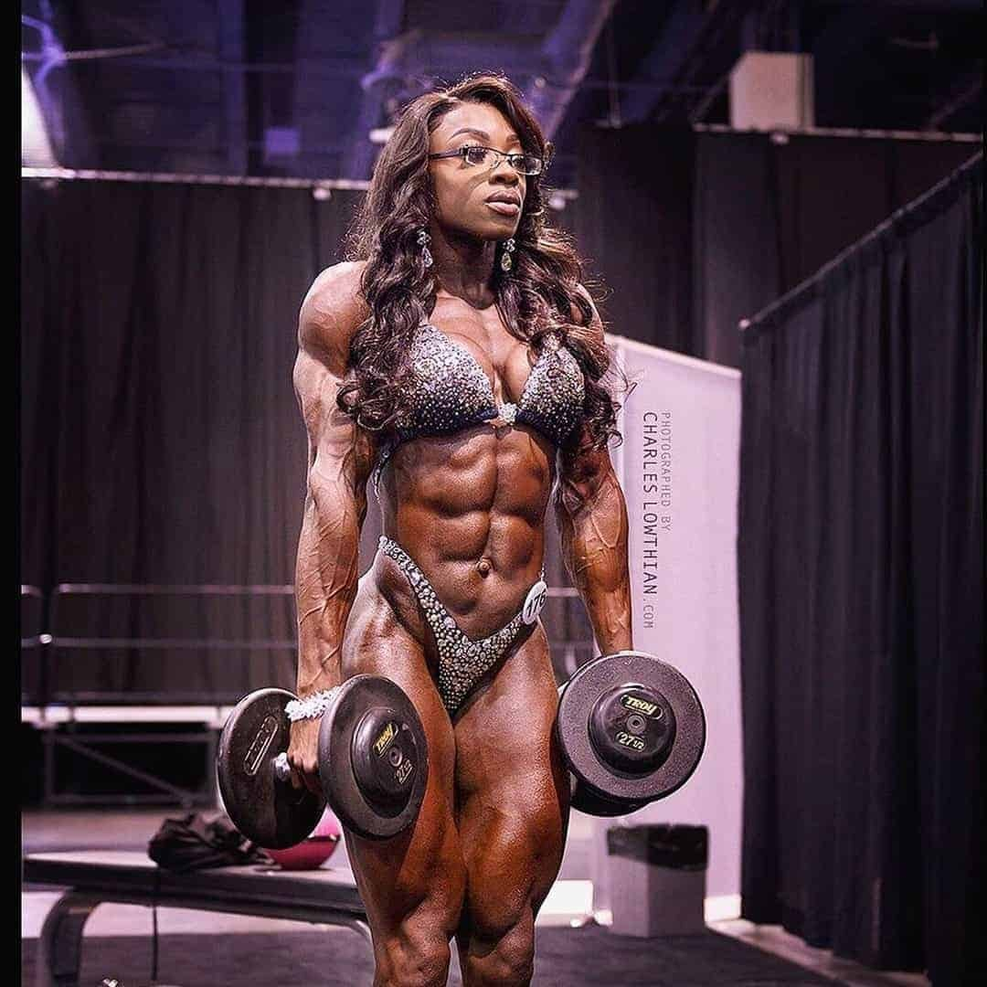 An image of Shanique Grant in the backstage of a competition, while lifting weights. SHe is wearing elegant, silver bikini set, and glasses on her eyes.