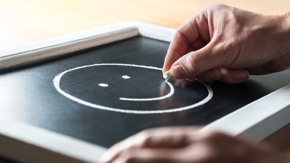 An image where someoen is drawing smiley on a small black table, with white chalk.