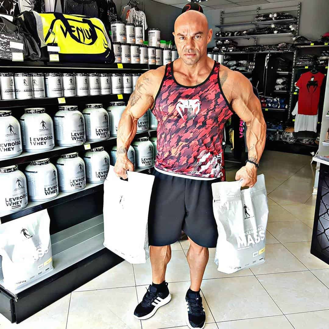Tose Zafriov in a supplements store, holding some bags with proteins. He is wearing t-shirt in red and black, and black shorts.