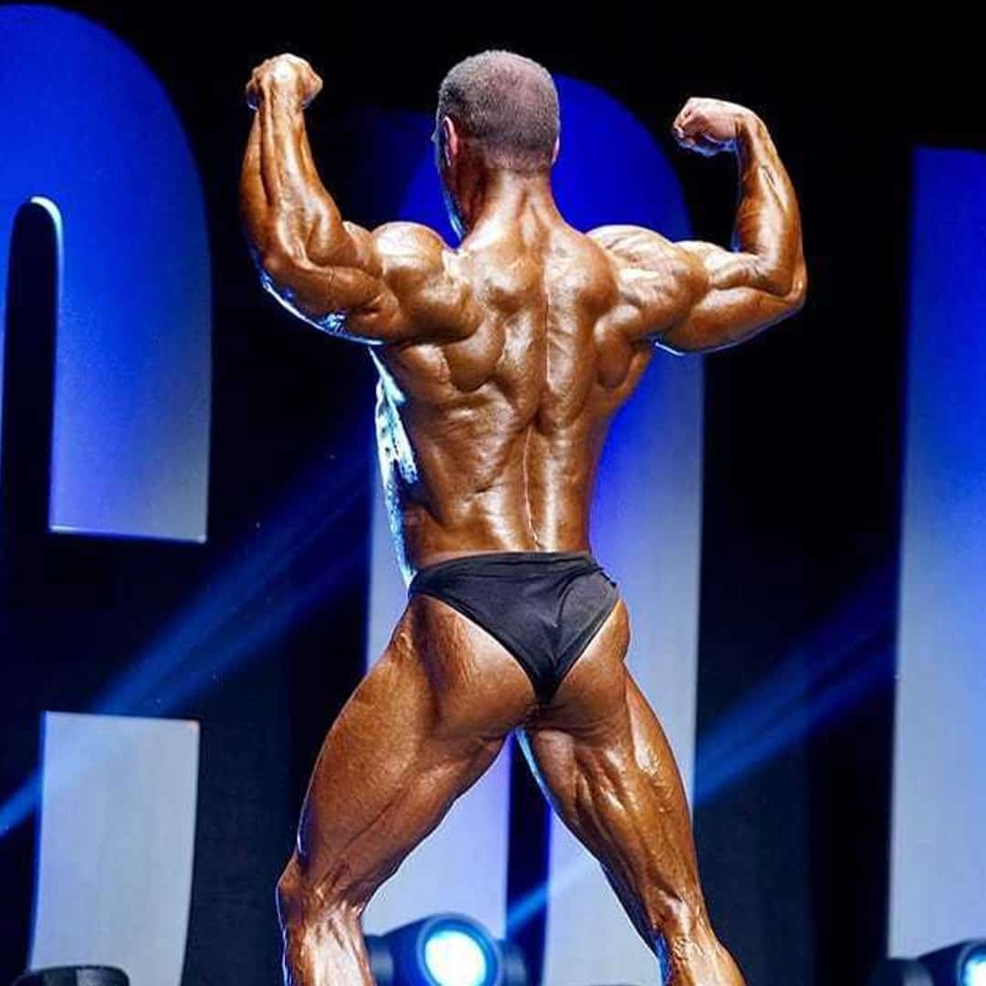 Ljubivoj Bakic flexing his muscles on stage where we can clearly see his back muscles. He is turned with his back in front of the camera, wearing navy blue trunks.