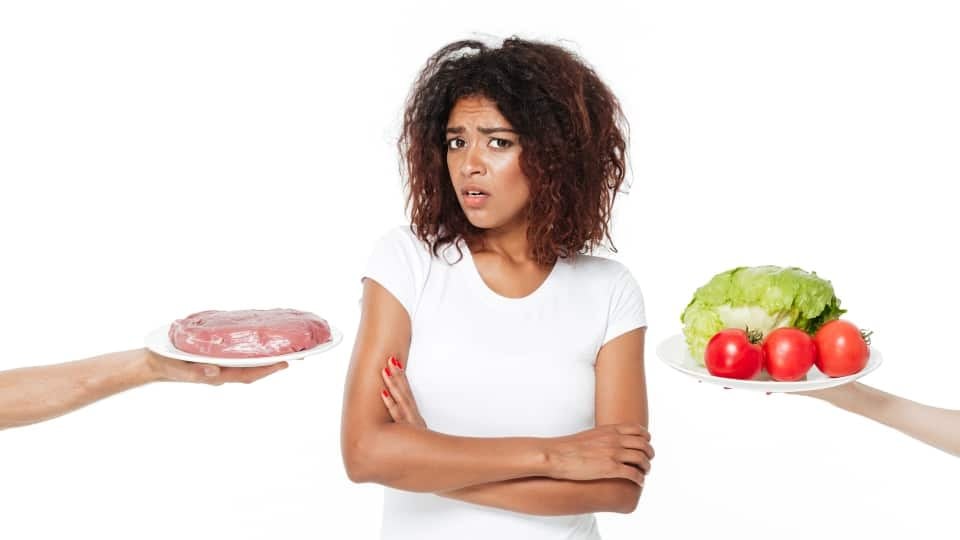An image of a girl in a white t-shirt and worried face expression who needs to pick between eating meat or eating vegetables to avoid making muscle-building mistakes, on a white background.