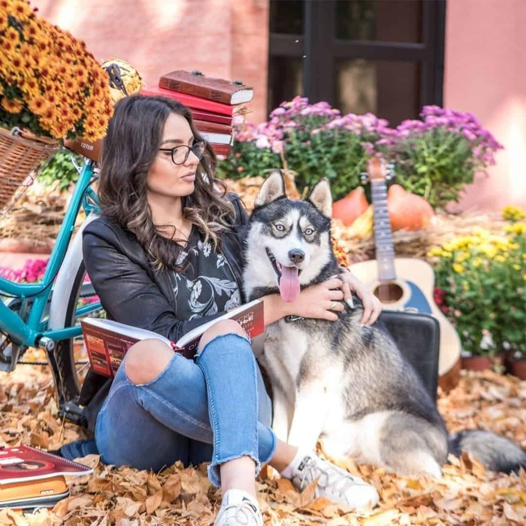 A woman sitting next to a haska dog, while hugging it. She is wearing black t-shirt and sunglasses. There is a bike, guitar and some followers in the background.
