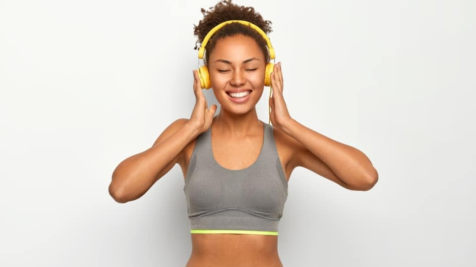 A girl listening to music on a yellow headphones, while smiling and wearing grey sports bra. There is a white background.