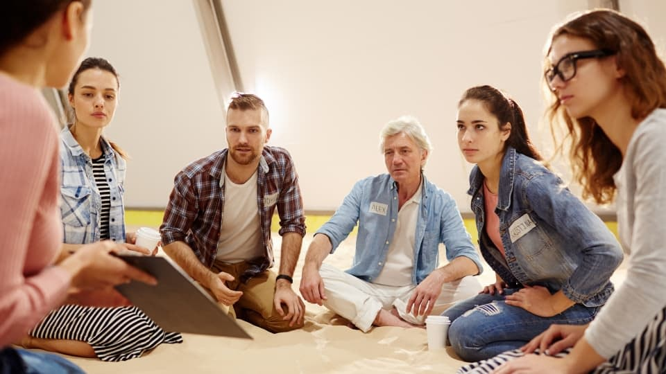 An image of a group of people discussing psychology and the mental training skills, while sitting on a floor.