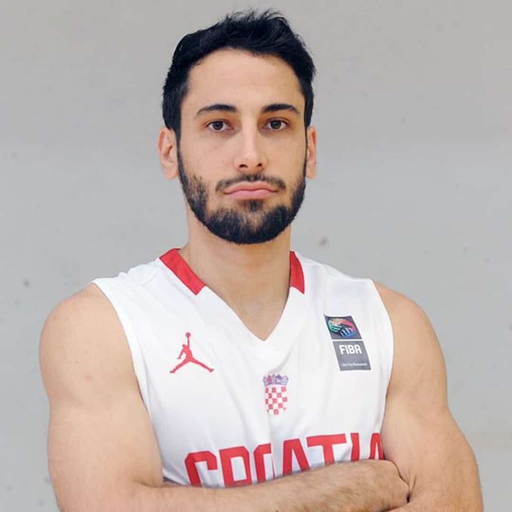 Rok Stipcevic, wearing a white jersey, behind him is a gray background.