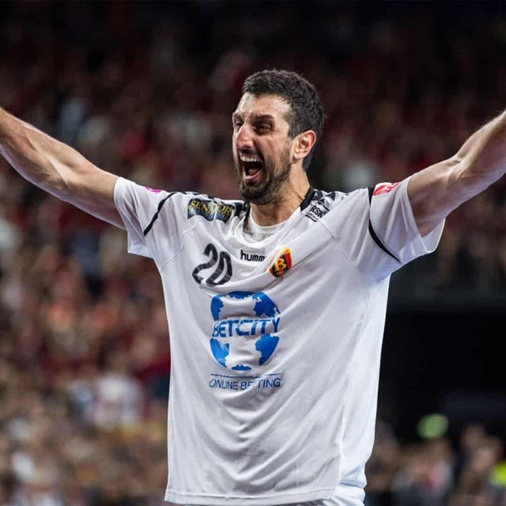 Ilija Abutovic wearing a white jersey and yelling in a joyful pose with laughter