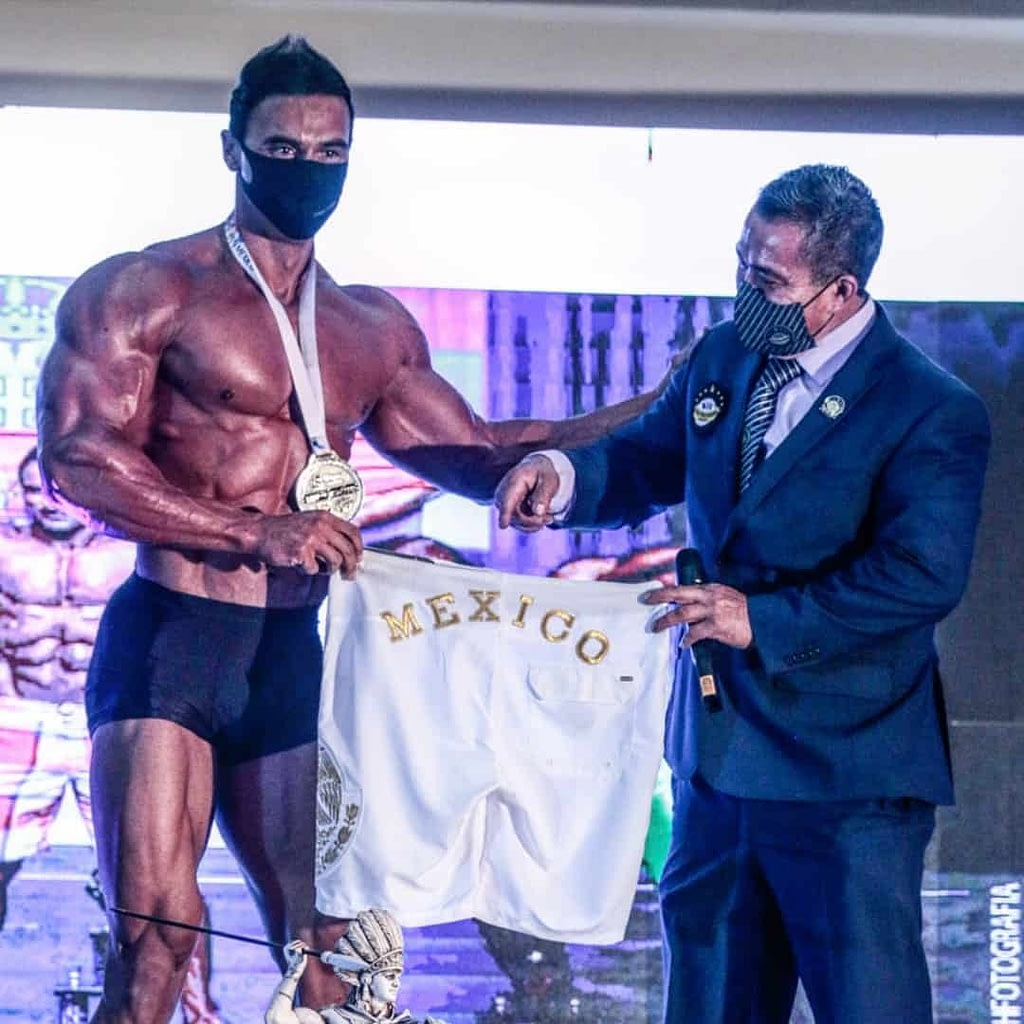 Branko Teodorovic receiving a white Mexico shirt from another man who is wearing a suit, at a competition where he has won a golden medal. He is without t-shirt, wearing black pants.