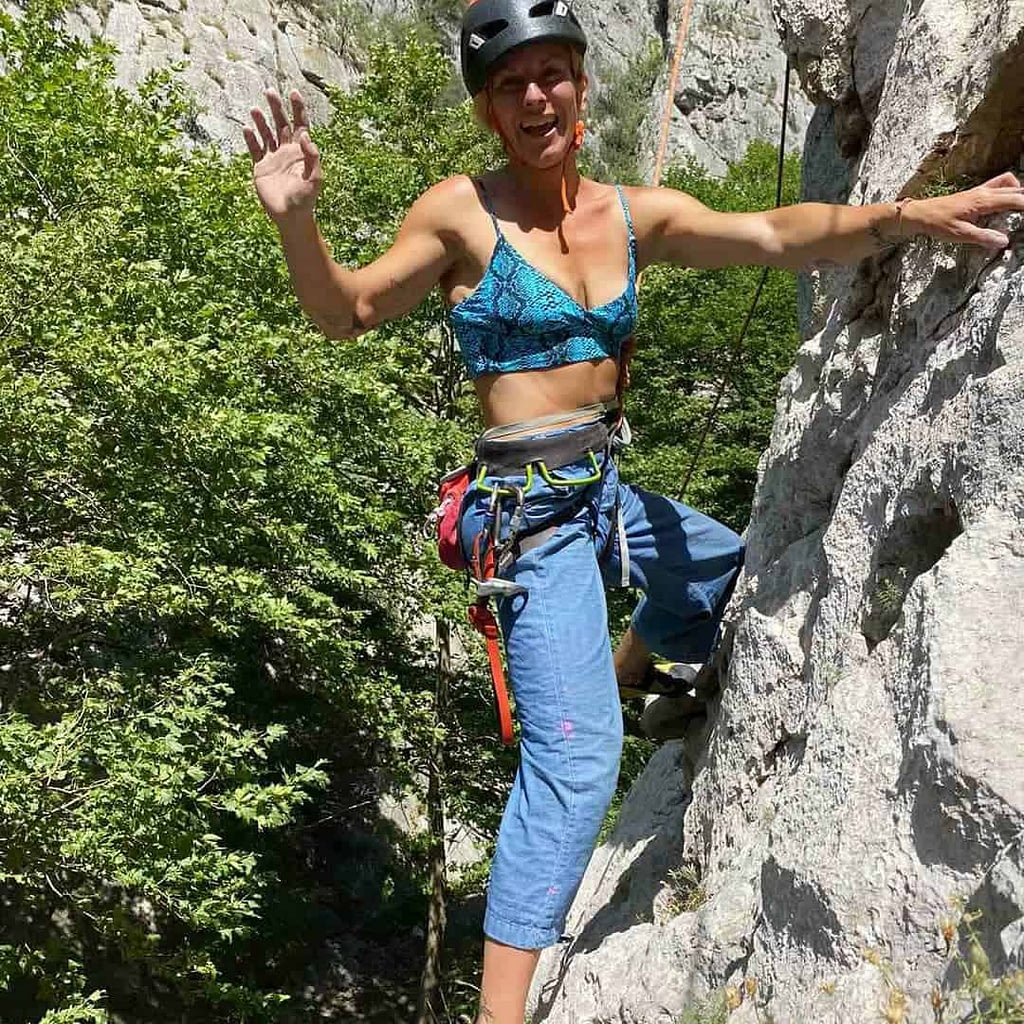 Ilina Arsova while hiking on a mountain rocks. She is wearing black protctive hat on her head, blue sports bra and some security bells. She is smiling.