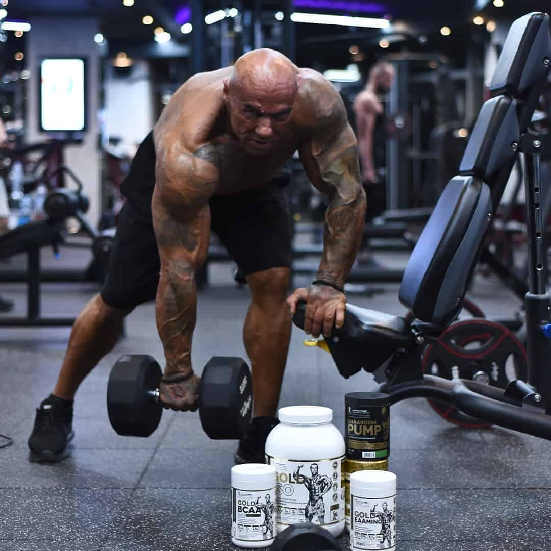 Tose Zafirov lifting weights in the Pulse Fitness Center, without t-shirt. There are some products from the gold and black line of Kevin Levrone.