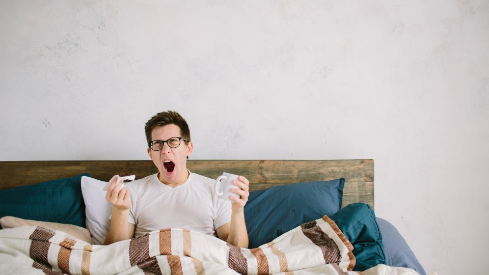 An image of a person waking up in the morning feeling tired in his bad, with his cup of coffee in his left hand.