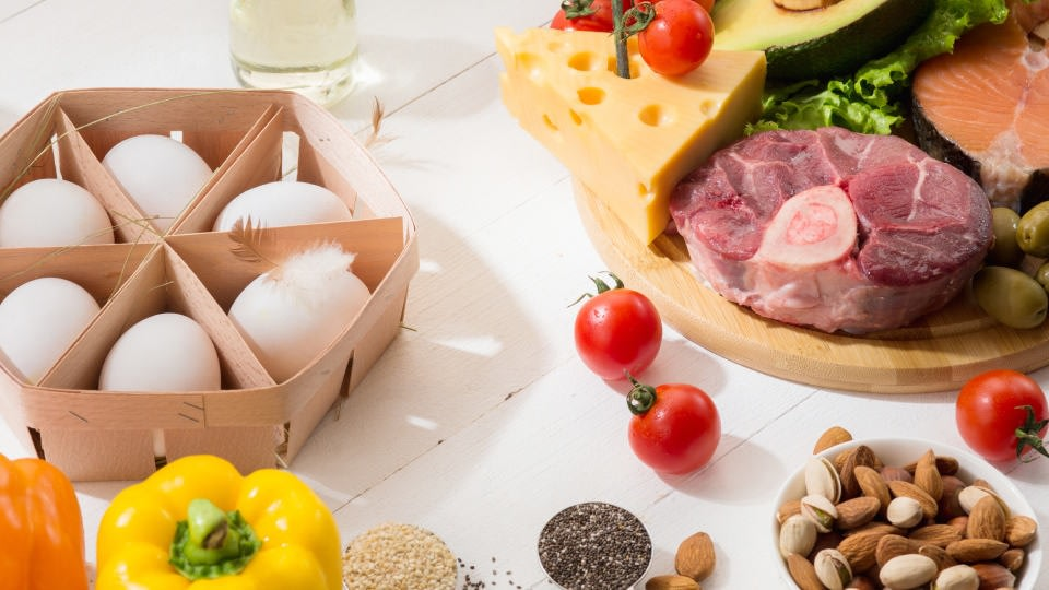 An image of meat as well as vegetables on a table, alongside eggs and cheese.