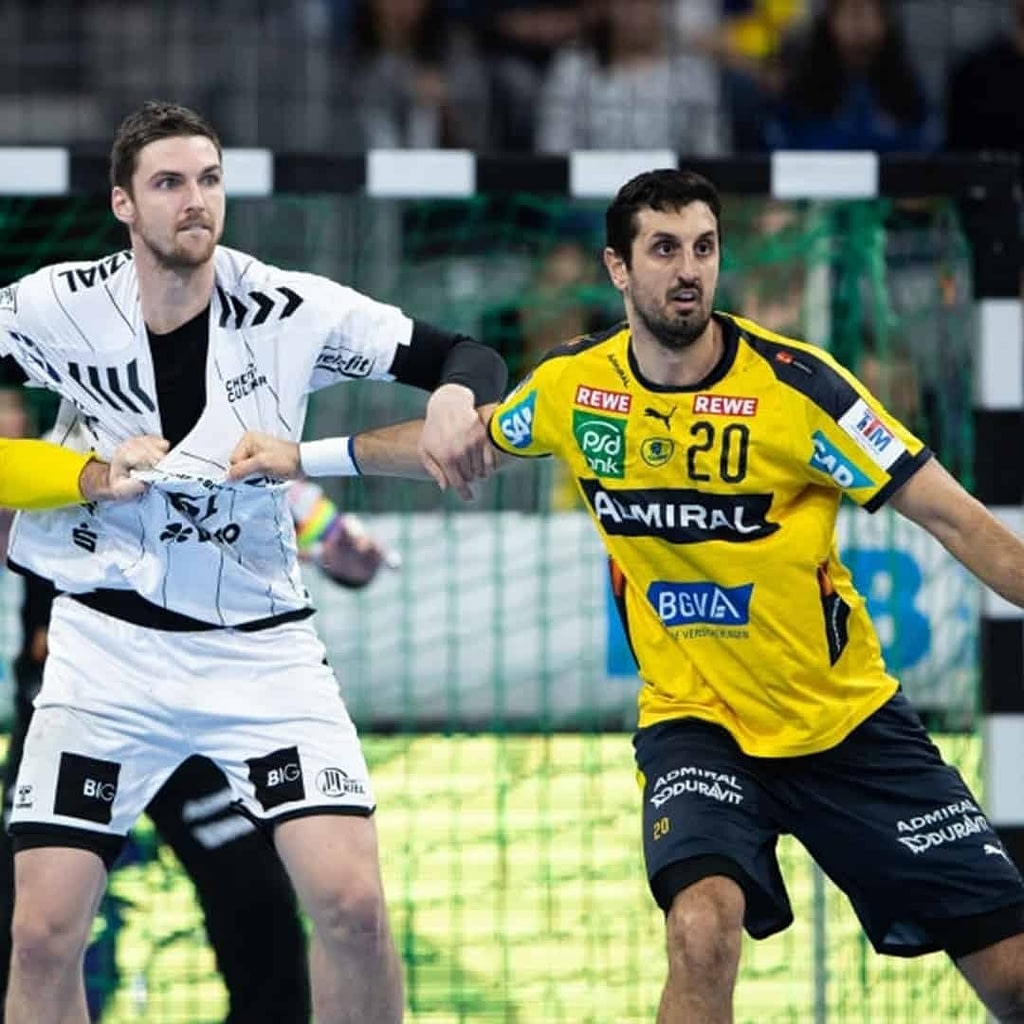Ilija Abutovic in a yellow jersey, in defending position at a handball game