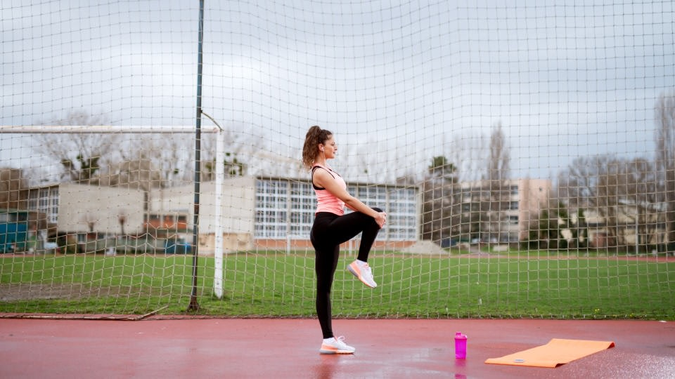 A woman training in a football field next to a yoga mat, stretching her leg. She is earing light pink t-shirt and black leggings.