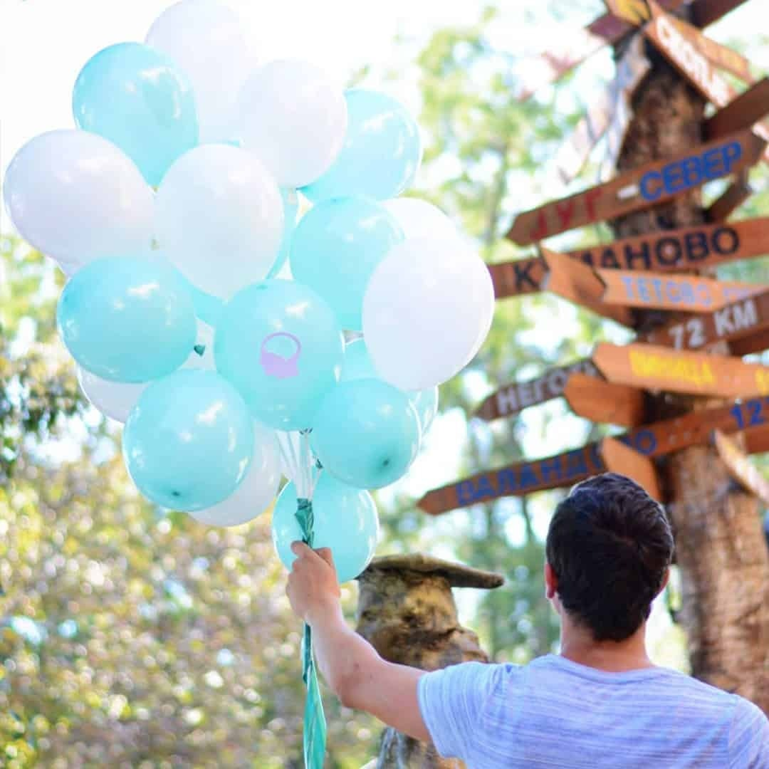 A man in a white t-shirt, with his back turned in front of the camera holding blue and white balloons filled in with helium, outdoor. There are some signposts in front of him.