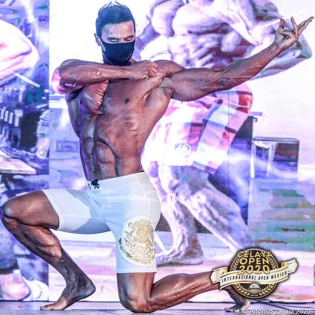 Branko Teodorovic presenting his body, on his knees, at the Celaya Open 2020 international competition. He is wearing white shorts, and he is without t-shirt. He is also wearing black mask on his face.