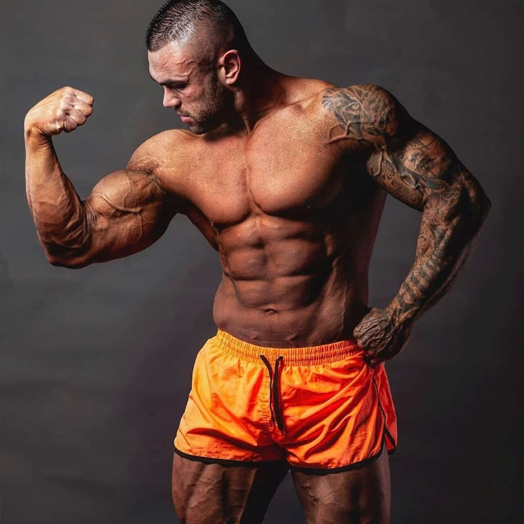 Hristijan Manasievski flexing his biceps muscles on a grey background, while wearing orange clothes, he has tattoos on his left hand entirely.