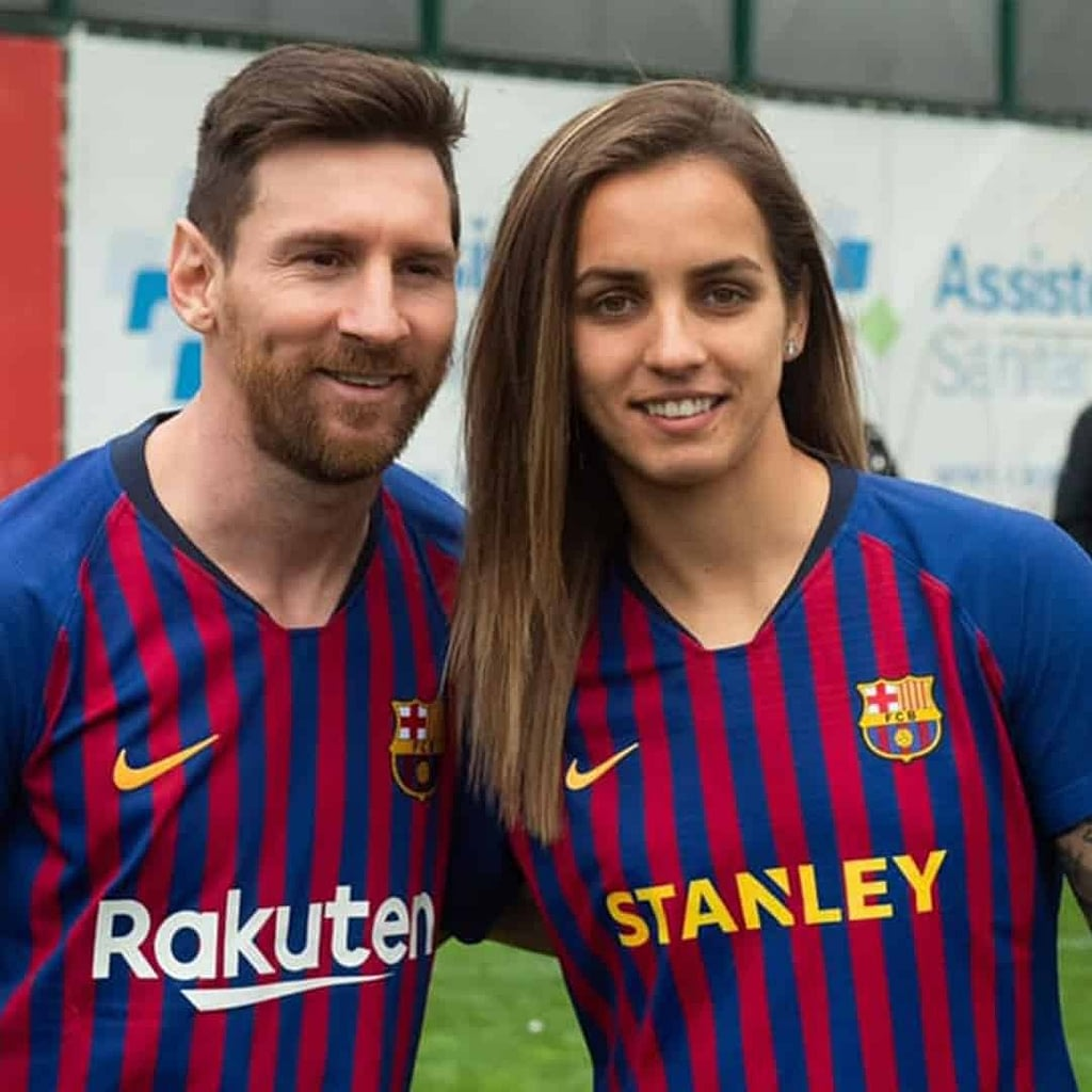 Lionel Messi and Natasa Andonova next to one another. They are smiling and wearing Barcelona jerseys.