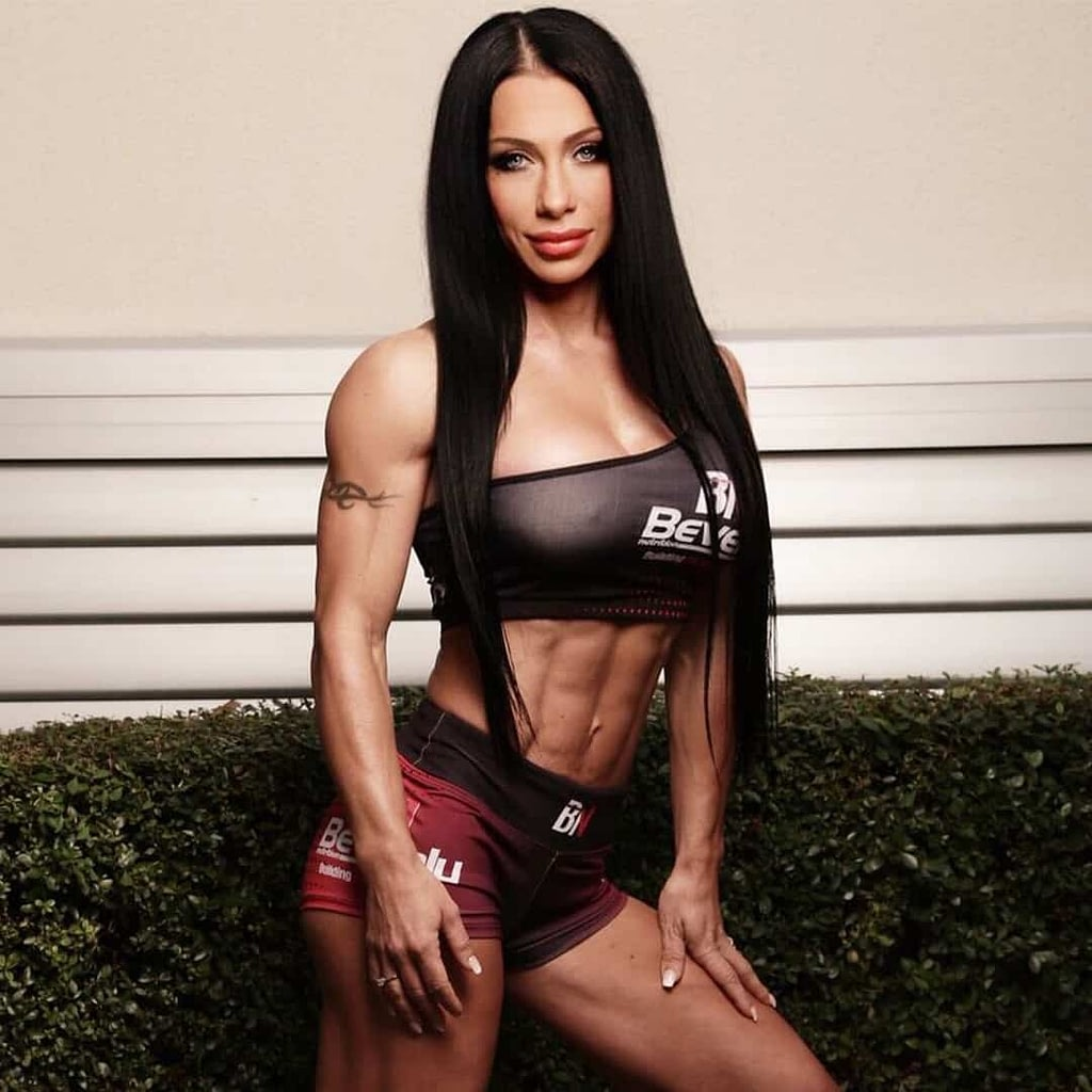 An image of Maria Bozinovska posing in front of a all, while wearing a black sports bra and red shorts.