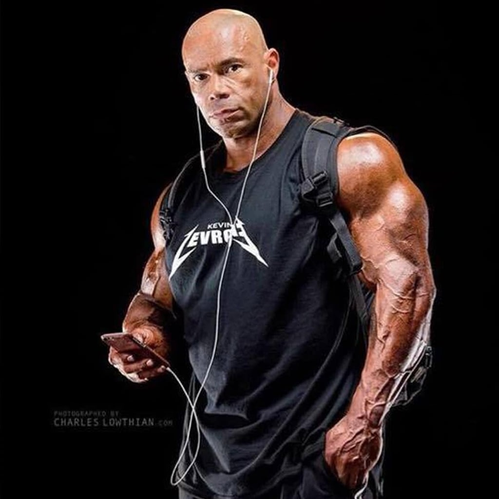 Kevin Levrone wearing his own merchandise shirt in a black colour and listening to music on his smartphone through white headphones