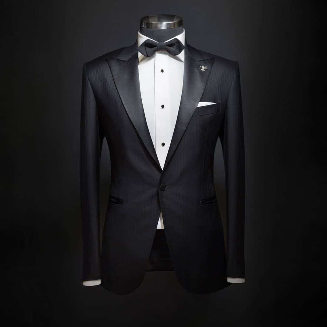 An image of an entire Suit setup from Signori in black colour in the form of a Tuxedo, with white shirt and black bow tie.