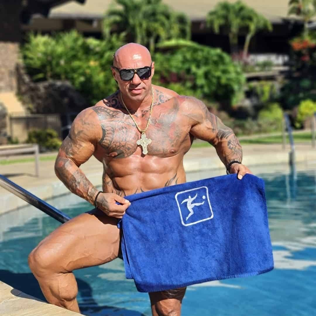 Tose Zafirov standing in a pool, with sunglasses on his eyes and holding a blue, sport life towel in front of him.