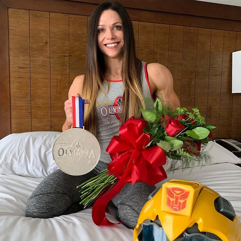 Oksana Grishina holding her Mr. Olympia medal with her right hand, and a bouquet of red roses in the other hand while being on top of the bed wearing a grey ''Mr. Olympia'' T-shirt