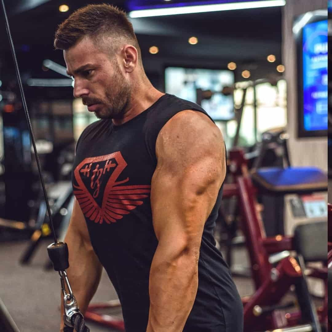 Trajche Stojanov training his triceps muscles at the gym. He is wearing a black t-shirt with red details.