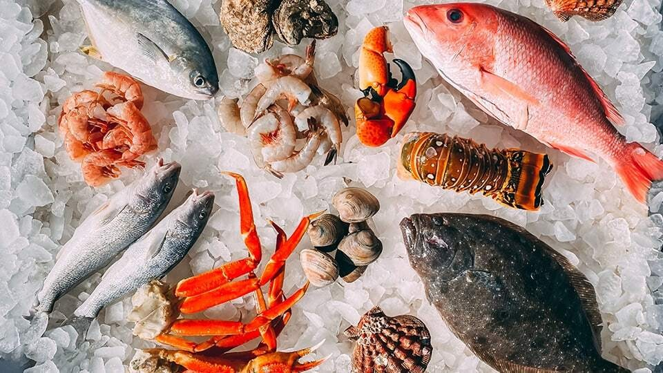 Different types of seafood including shrimp, lobster, and clams in ice.