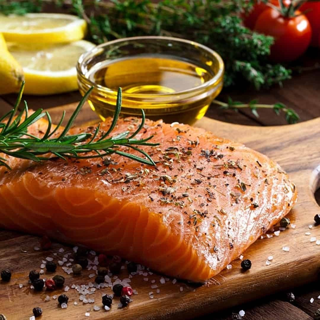 An image of a salmon on a wooden plate, with olive oil and lemons next to it.