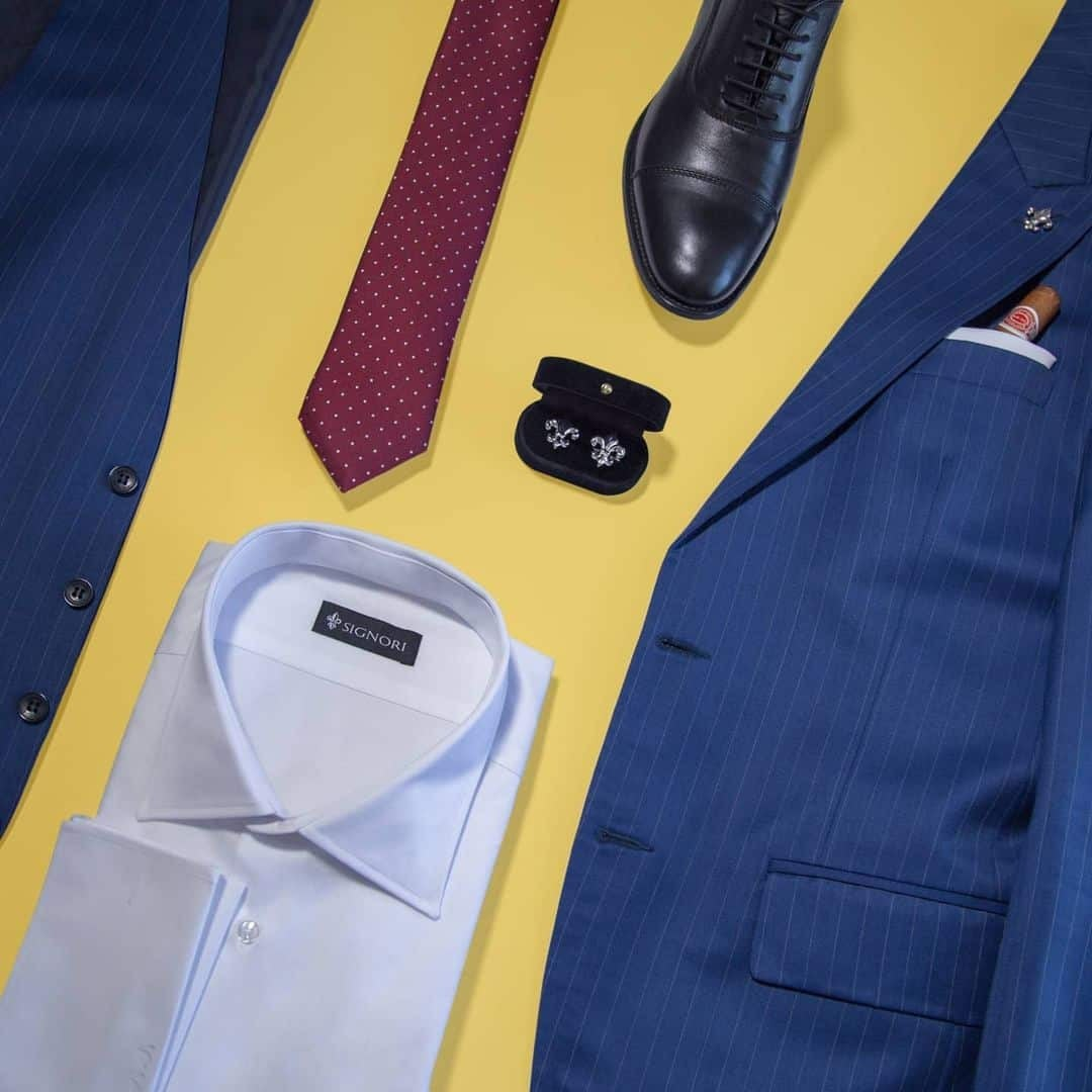 An image of a suit in navy blue colour, tohert with elegant , navy blue vest, white shirt, burgundy tie with white dots and black elegant shoes on yellow background.