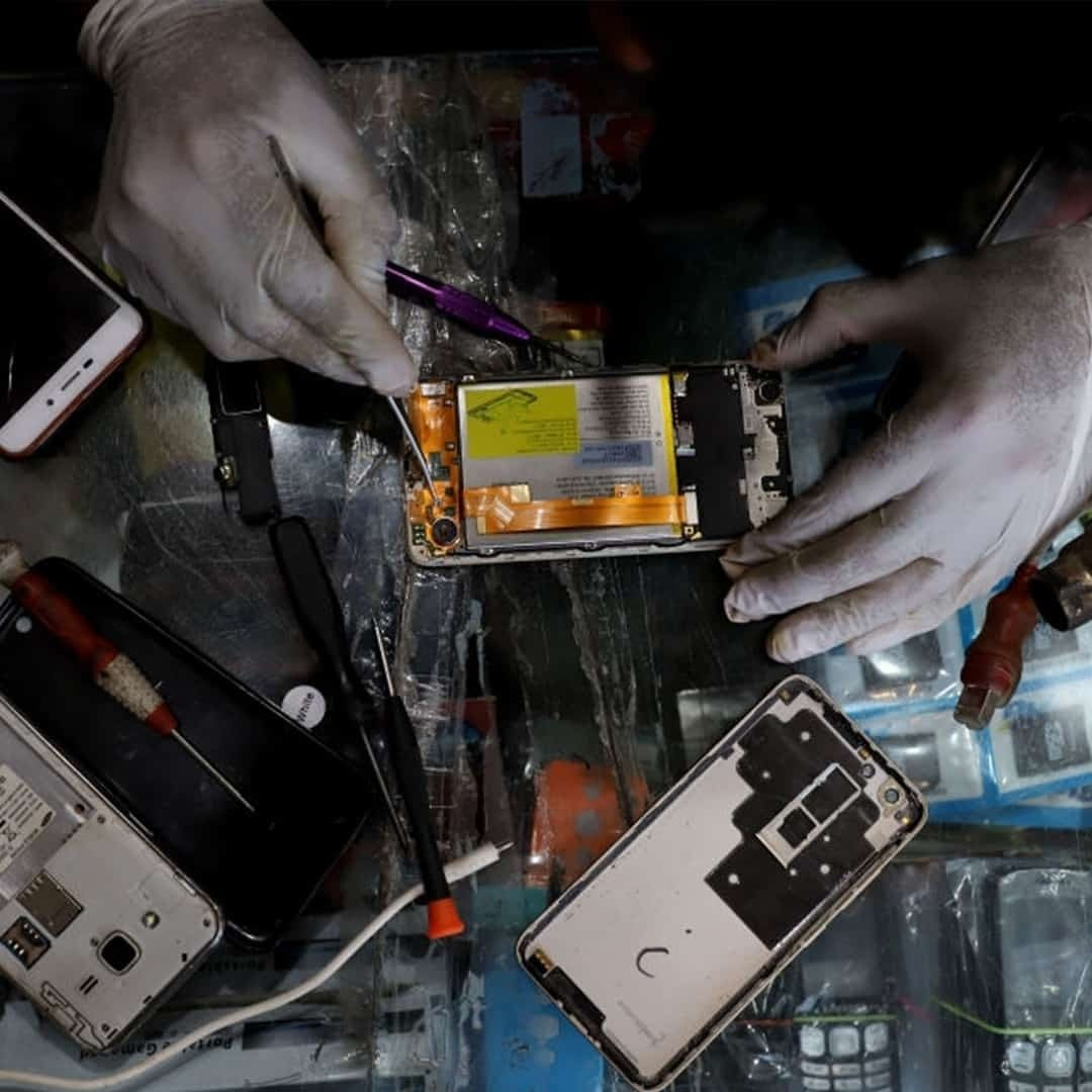 An image of hands with white medical gloves, repairing an open smartphone.