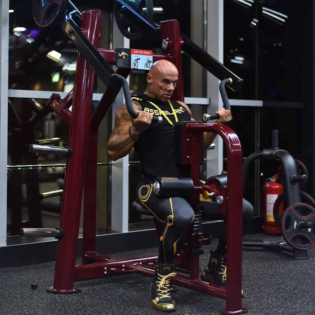 Tose Zafriov in a black t-shirt with hood, and black leggings, both with yellow details, doing exercises for his back in the gym.