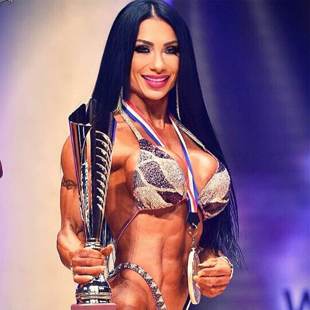 Maria Bozinovska on stage on a competition, with her award in her hands, and medal on her neck. She is wearing elegant bikini set, adn she is smiling.