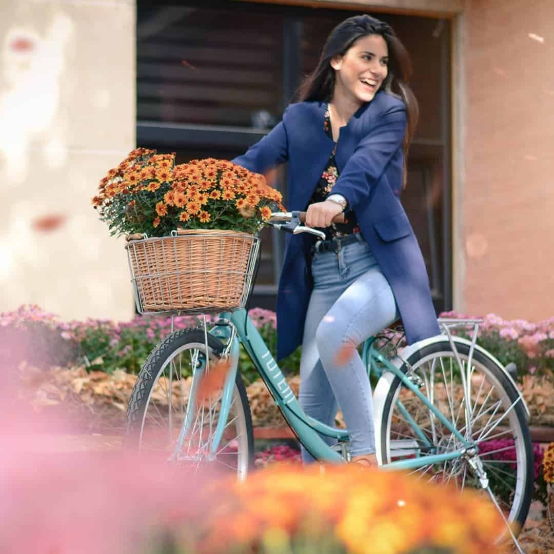 A woman riding her bicycle at the International Slavic University G. R. Derzhavin Campus, while smiling. She is wearing a navy blue coat and jeans.