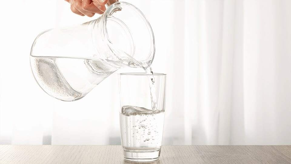 Water being poured into a glass, on a grey desk. There are white curations in the background.