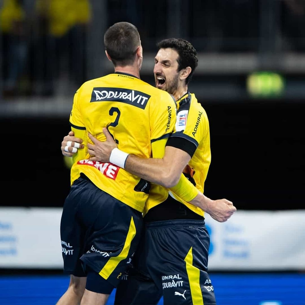 Ilija Abutovic huggging his teammate at a handball tournament with the number 2 on the back of the teammate. They are both wearing yellow jerseys.