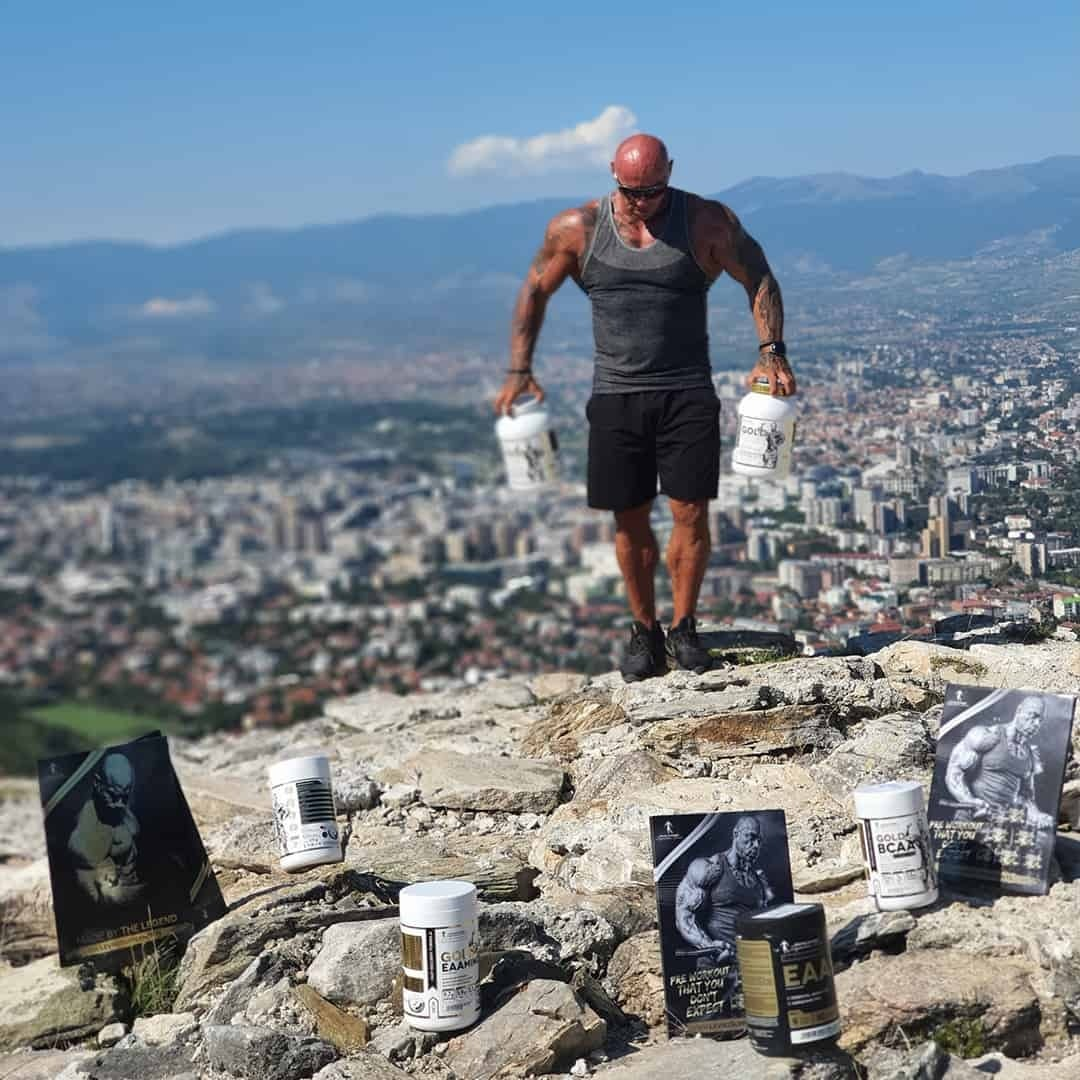 Tose Zafirov on top of Skopje holding the Kevin Levrone Signature Series supplements. He is wearing dark grey t-shirt and black shorts, and sunglasses on his eyes.