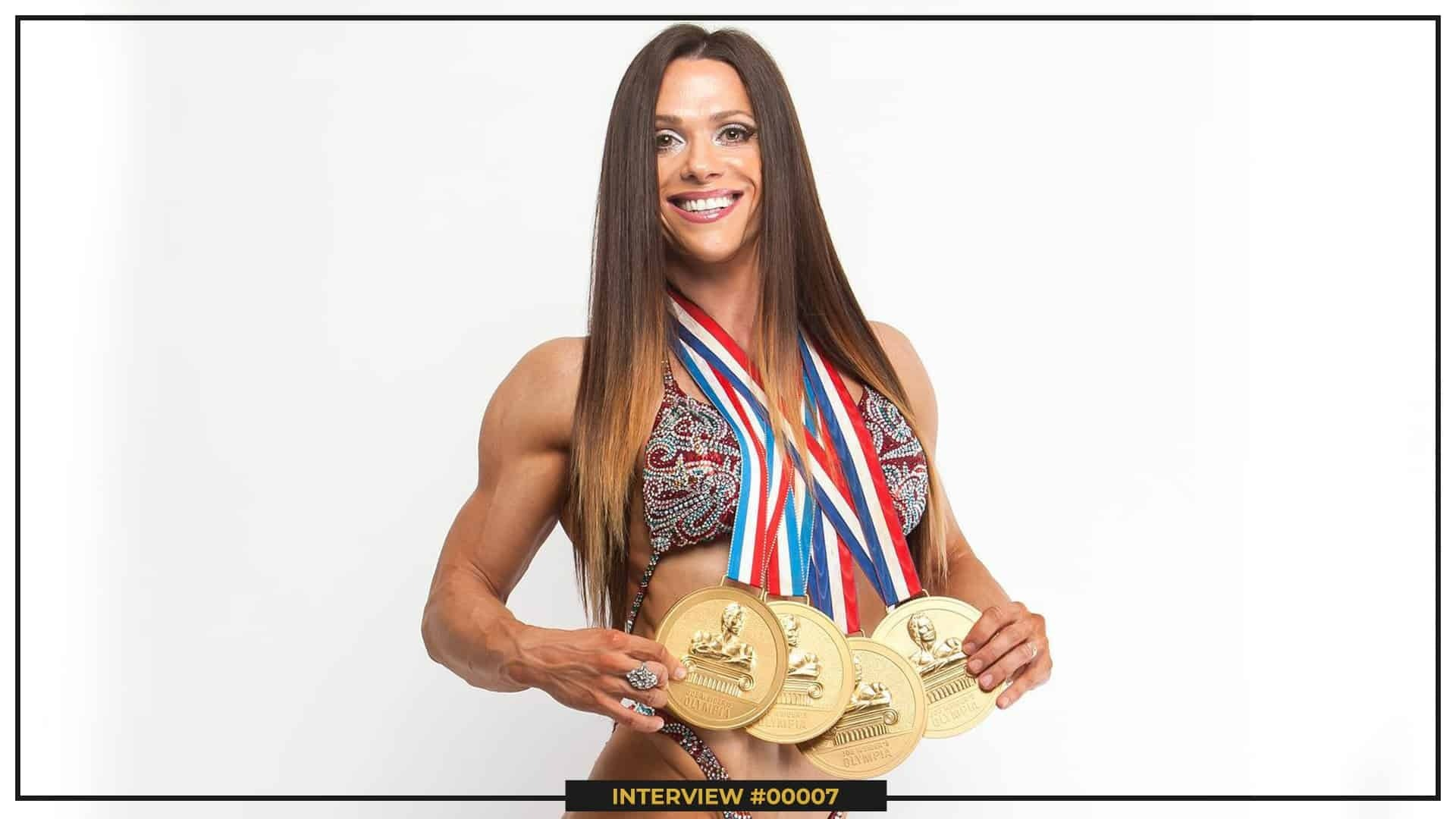 Oksana Grishina standing in front of the camera, smiling and holding her four golden ''Mr. Olympia'' medals, on a white backgound.